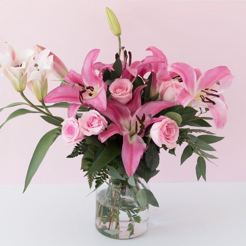 Kukkakimppu vaaleanpunaisia liljoja ruusujen kanssa